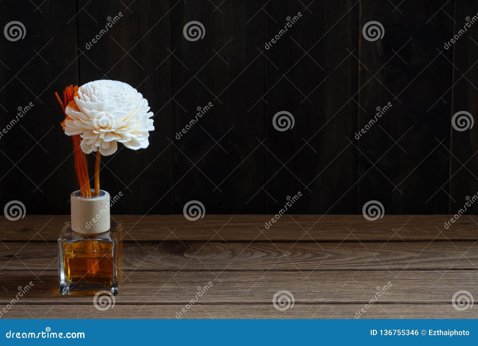 Aromatisches Reederfrischungsmittel, Duft-Diffusor-Satz der Flasche mit Aroma haftet Reeddiffusoren auf dunklem hölzernem Wandhin