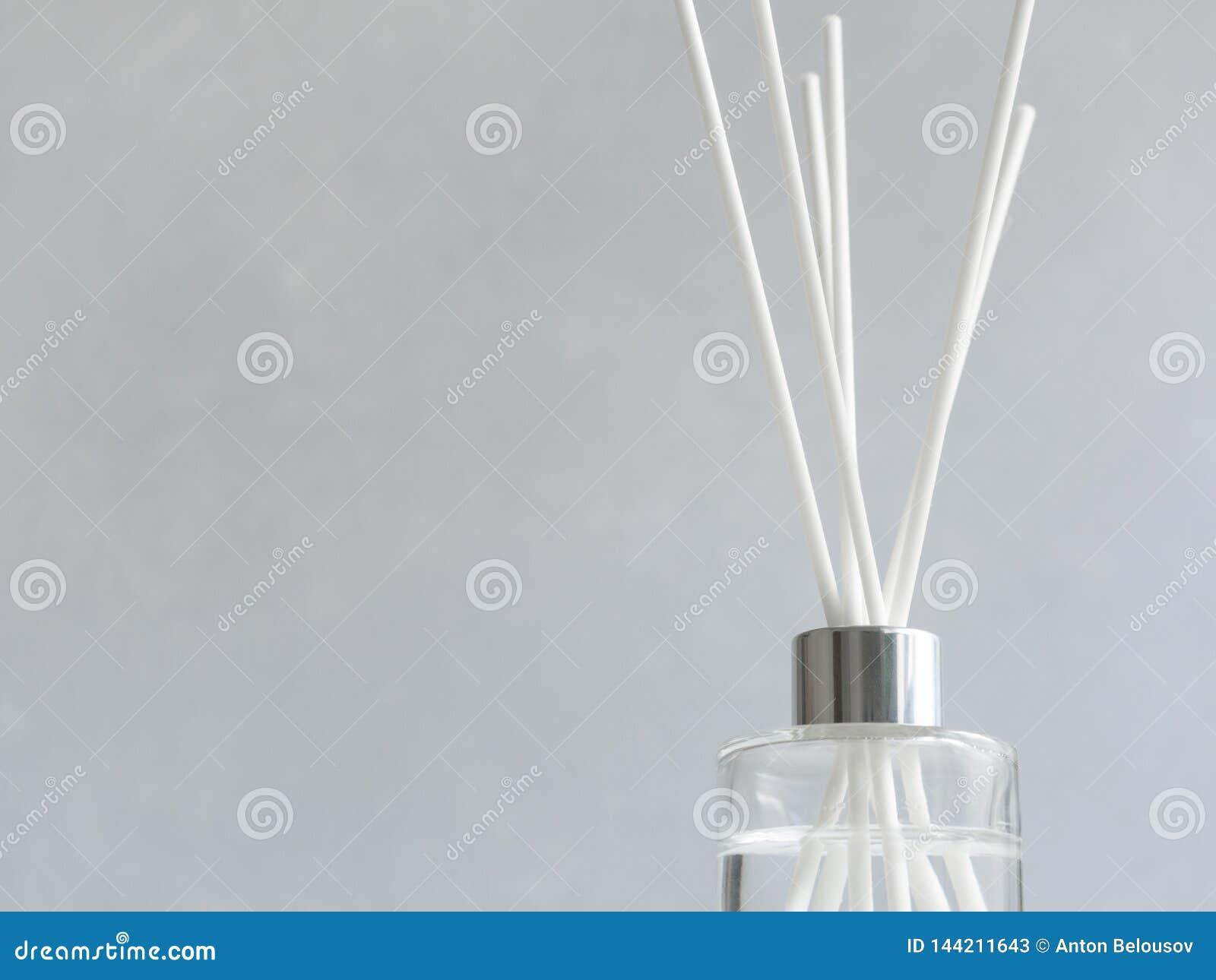 Aromatizador Refrogerador de ar aromático em uma garrafa de vidro transparente com juncos brancos em um fundo cinzento