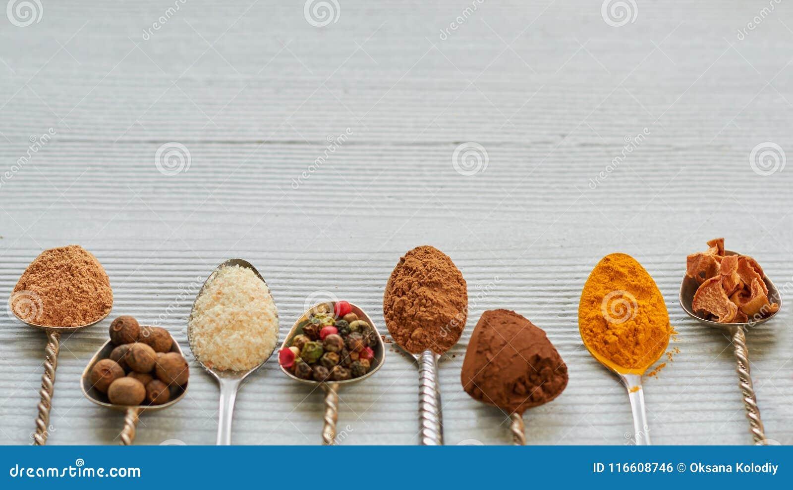 Aromatyczne Indiańskie pikantność i ziele na metal łyżkach: gwiazdowy anyż, fragrant pieprz, cynamon, asafetyda, turmeric Pikantn