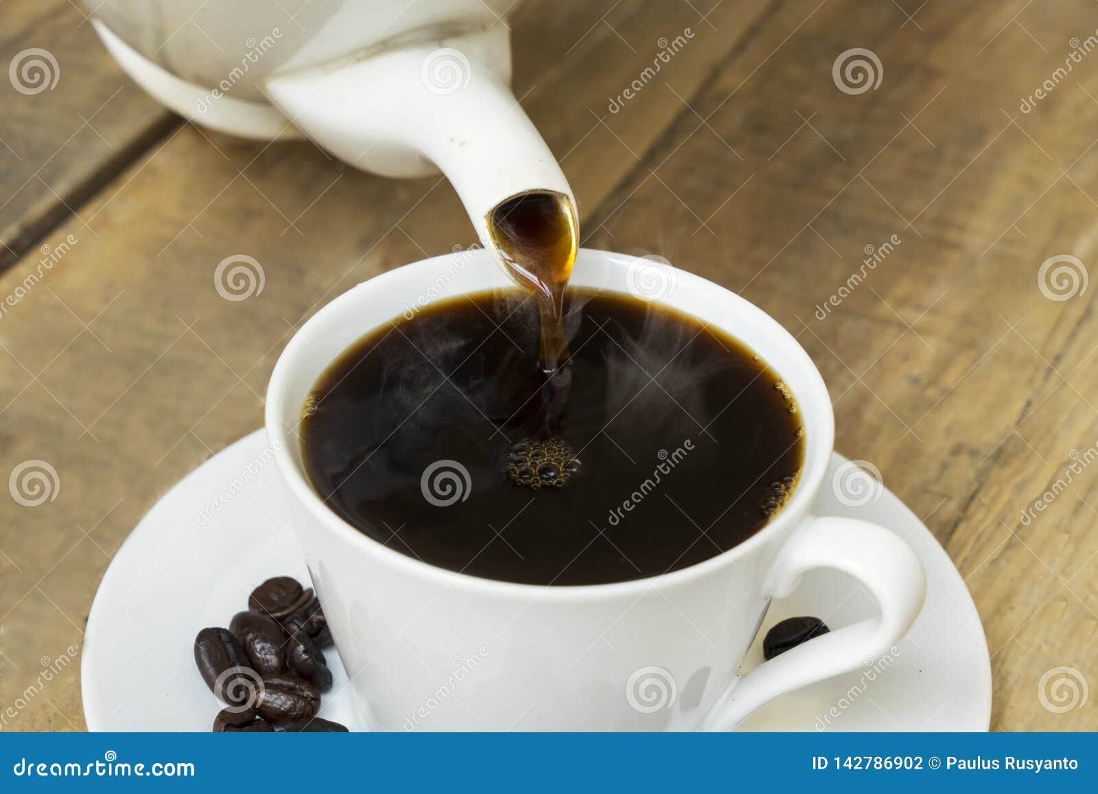 Aromatyczny kawowy dolewanie w filiżankę na stole