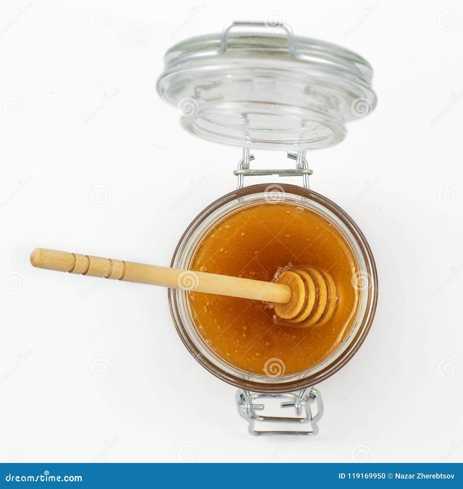 Aromatyczny miód z chochlą w słój odizolowywającego na białym tle Odgórny widok