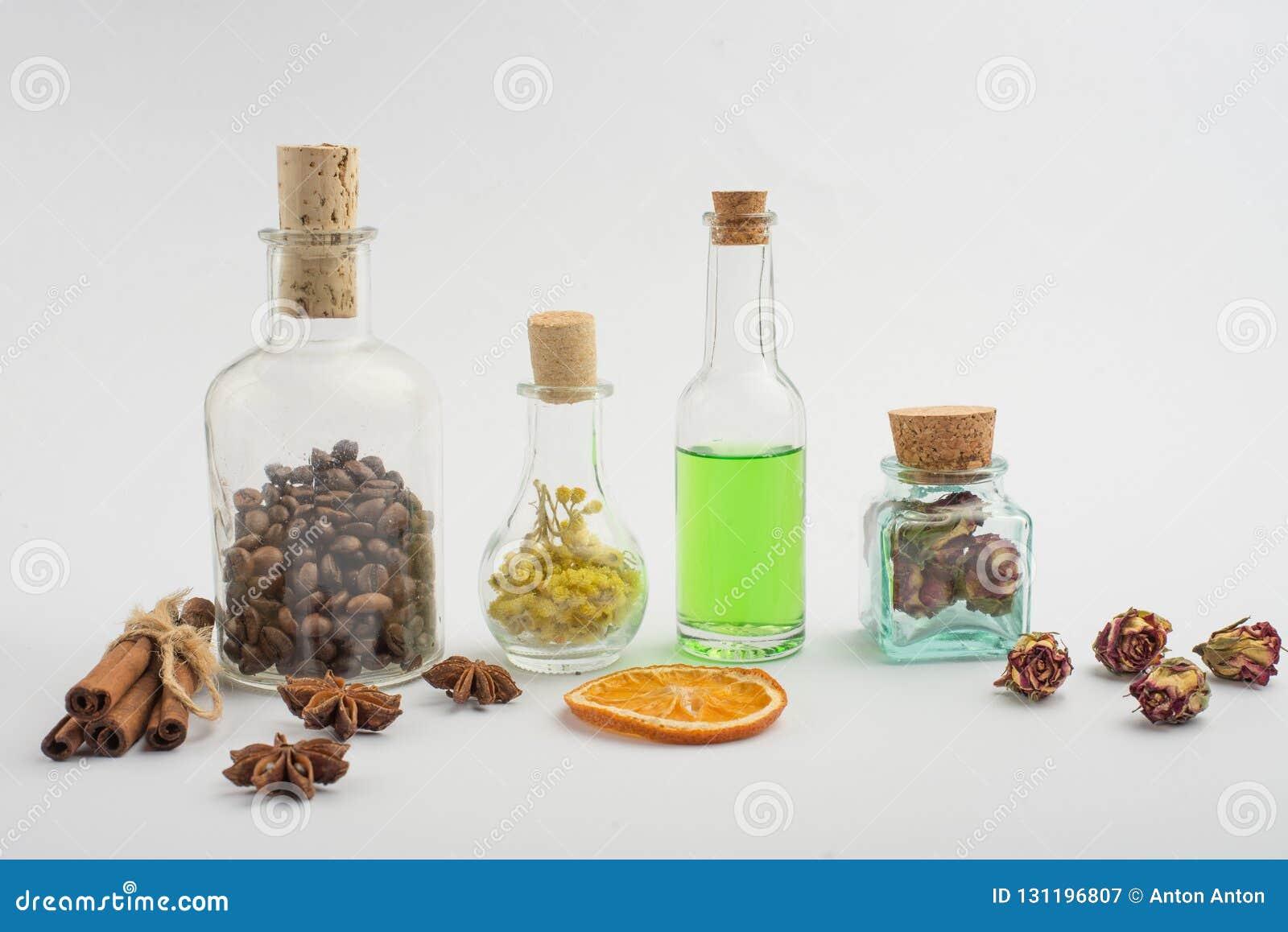 Aromatyczny olej, kawa groszkuje, aromatów ziele w szklanych butelkach na lekkim tle, Pojęcie ciała piękno i opieka