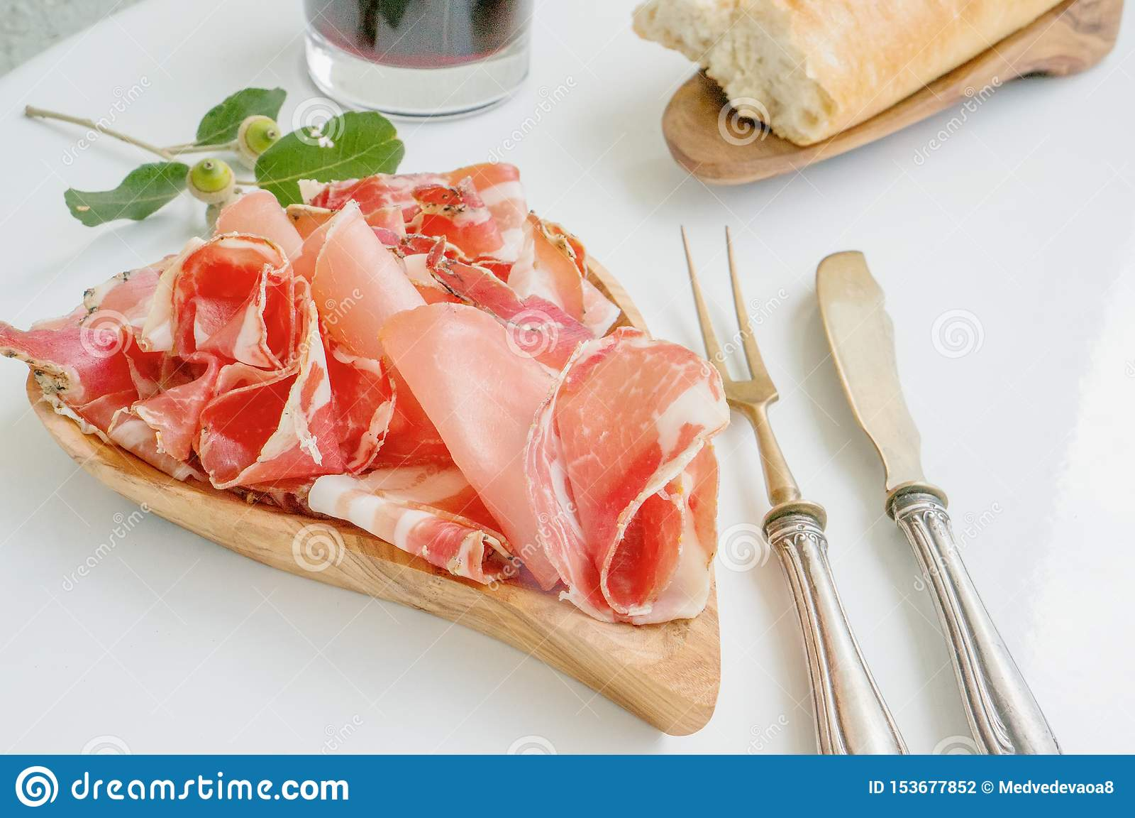 Aromen av skinka och kryddor som skivas tunt på en vit tabell med bestick och rött vin för bröd antikt