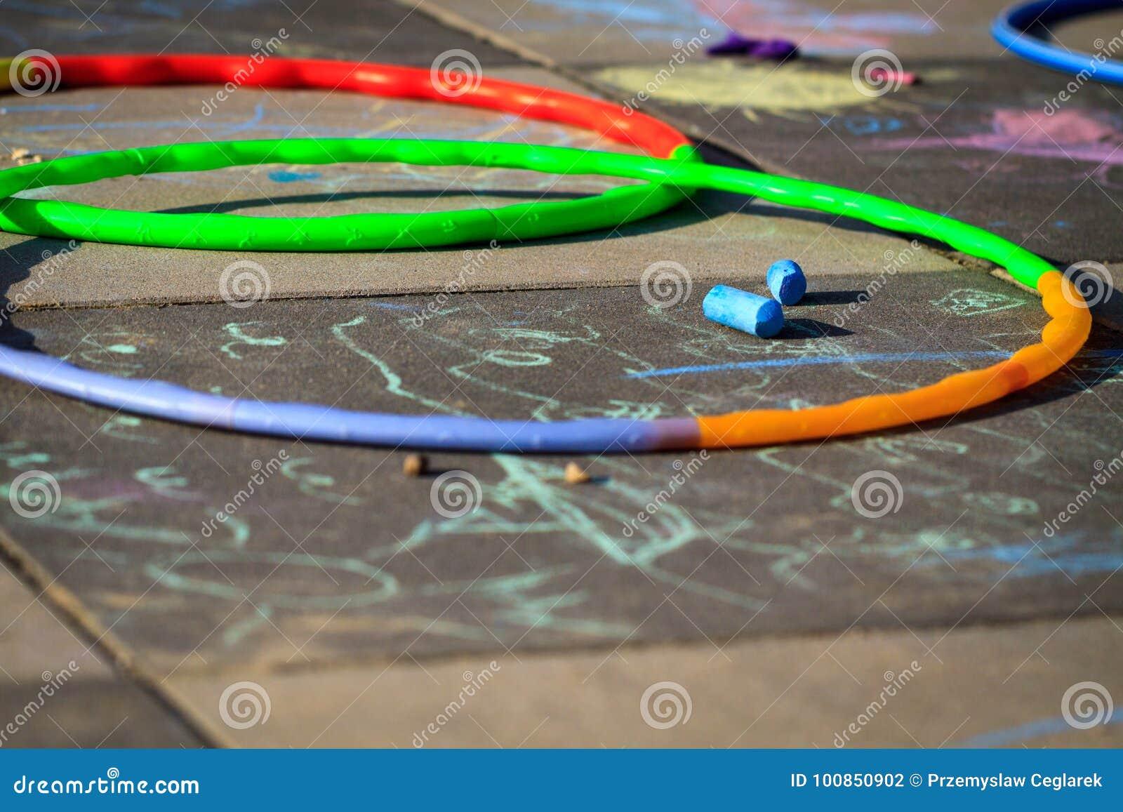 Aros pequenas do hula do jogo da menina no campo de jogos