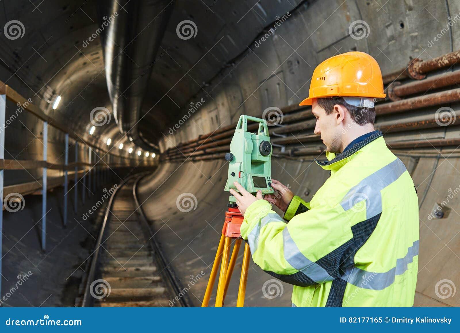Arpenteur avec le niveau de théodolite aux travaux de construction de tunnel de chemin de fer au fond