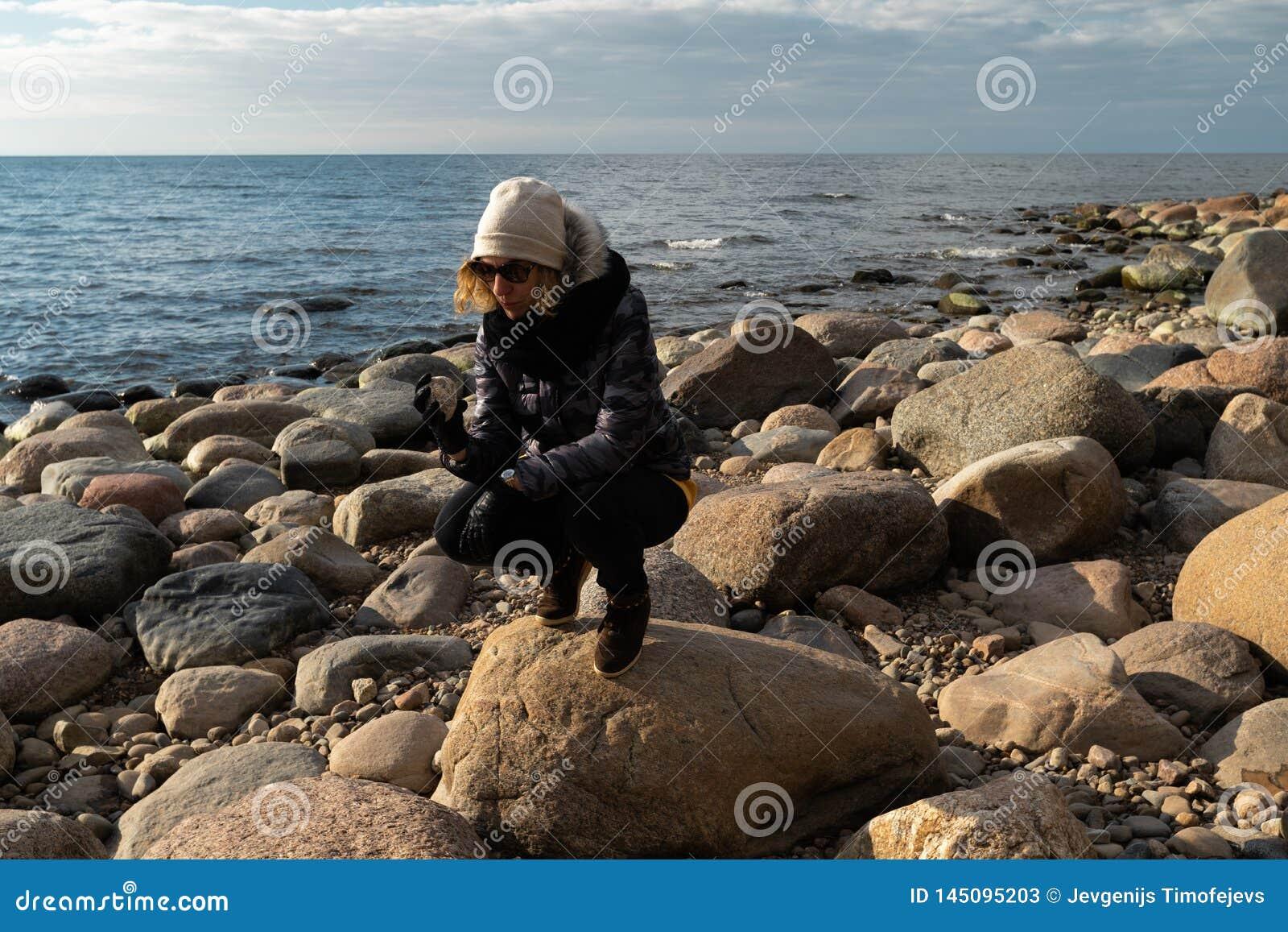 Arqueólogo joven en una playa del canto rodado que busca rocas exóticas en una costa costa de un mar Báltico