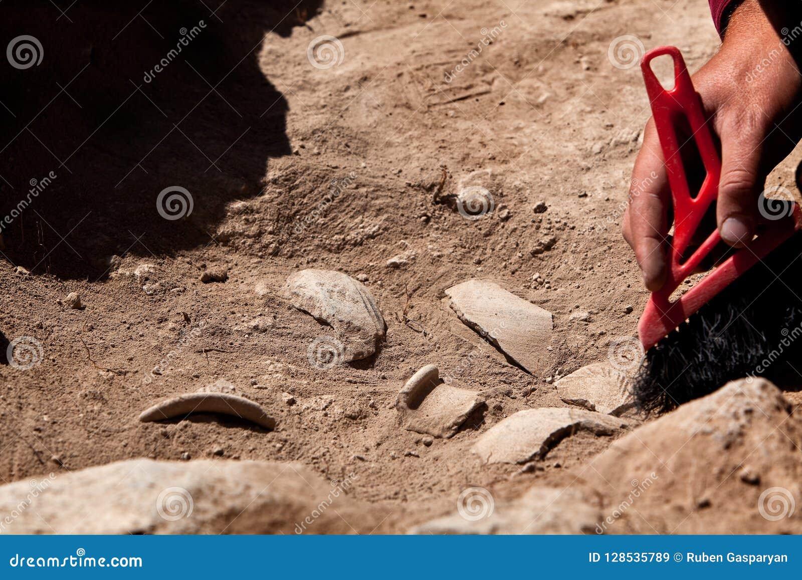 Arqueólogo que trabaja en el sitio, mano con el cepillo