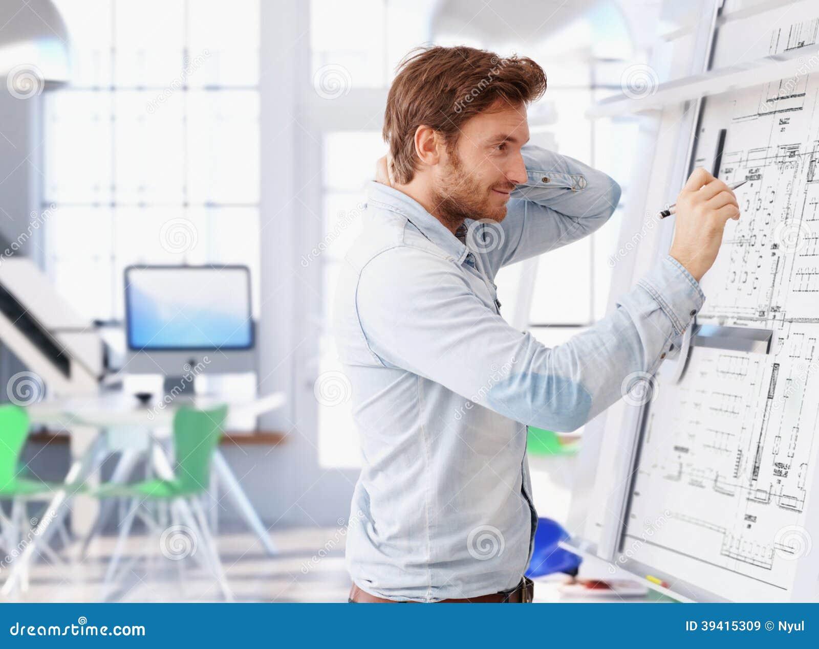 Arquitecto joven que trabaja en el tablero de dibujo foto for Todo para el arquitecto