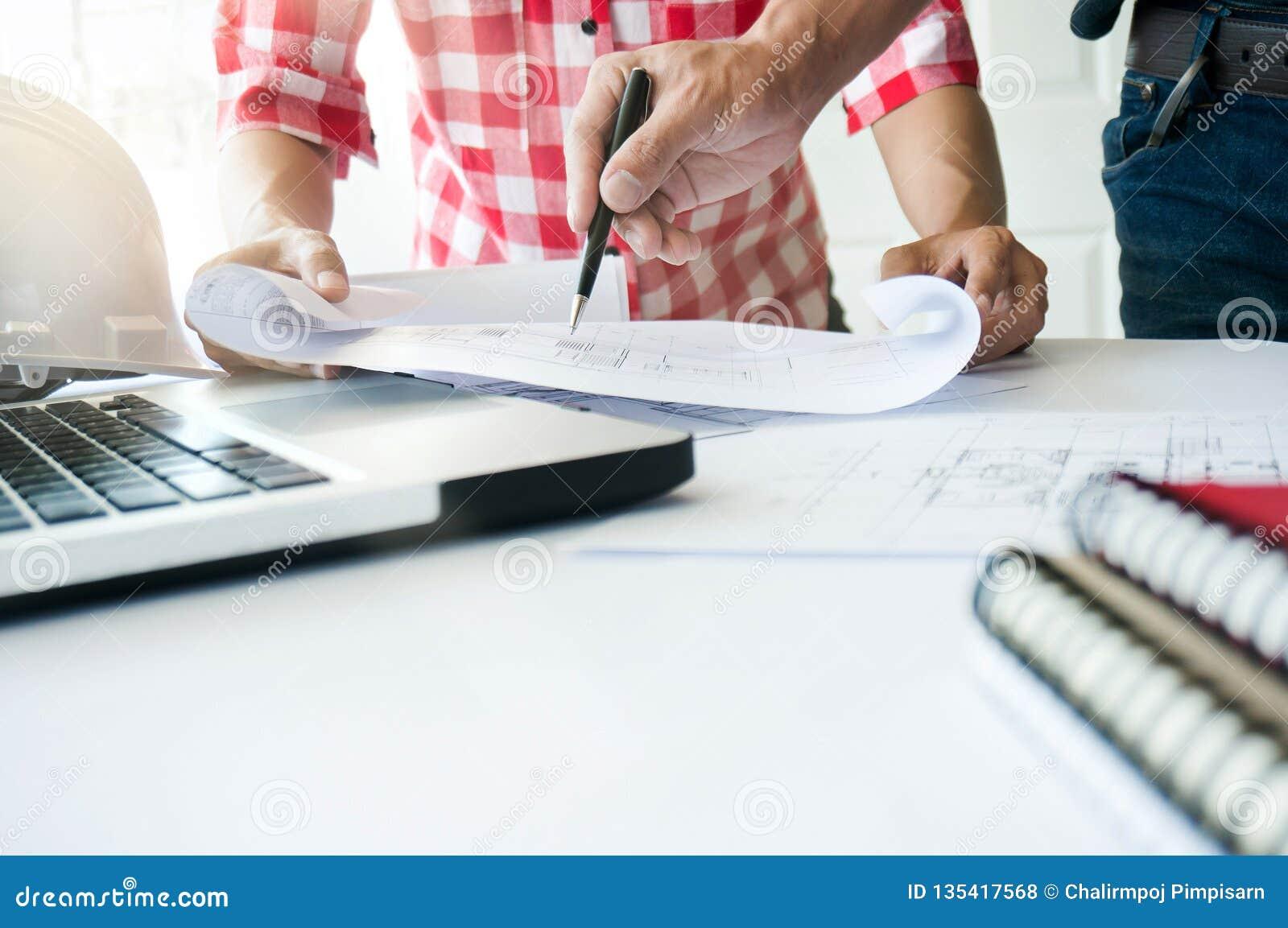 Arquitectos que trabajan en proyecto de edificio del modelo junto concepto del trabajo de Team del ingeniero