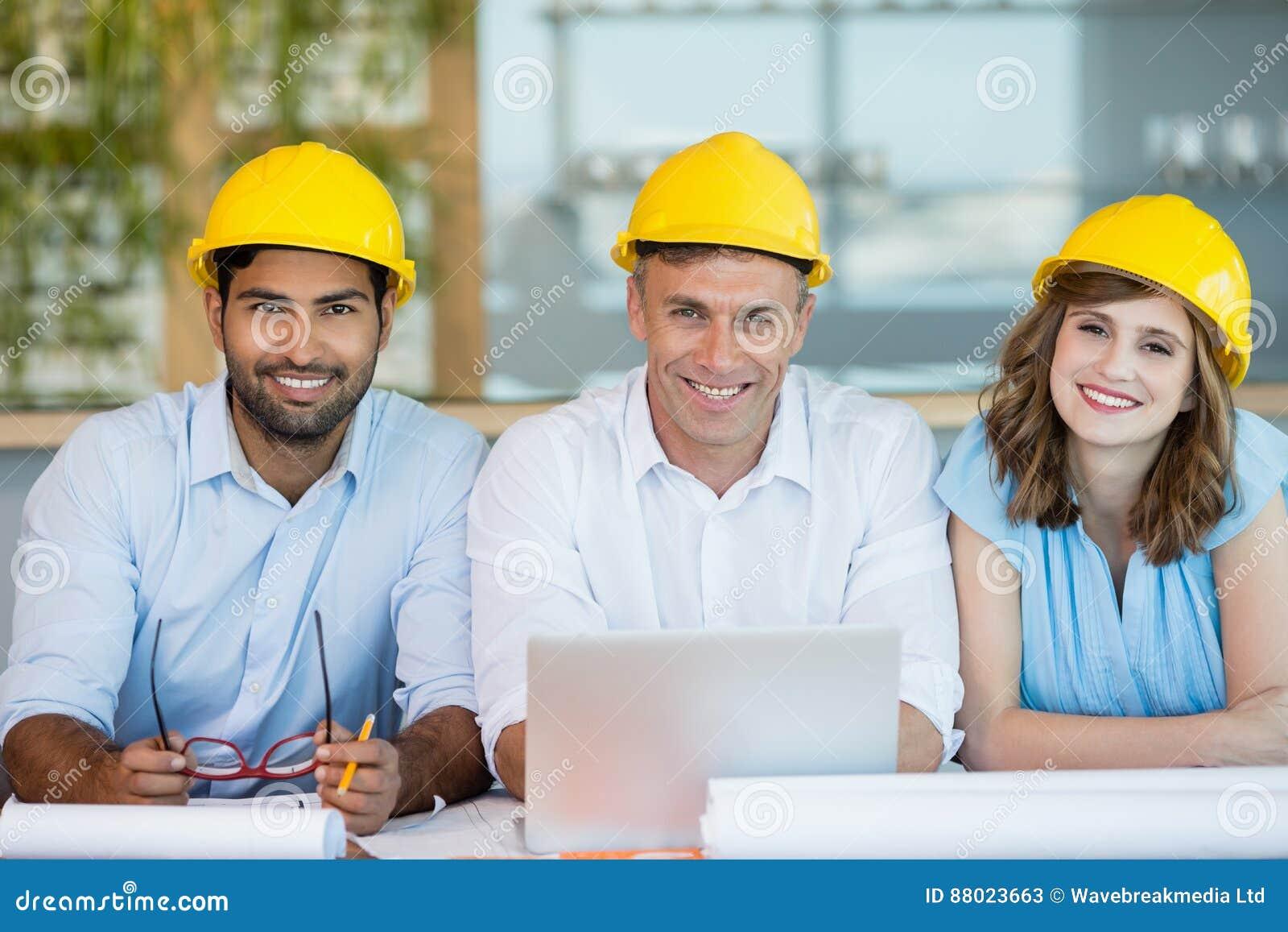 Arquitectos sonrientes que se sientan junto en la sala de conferencias