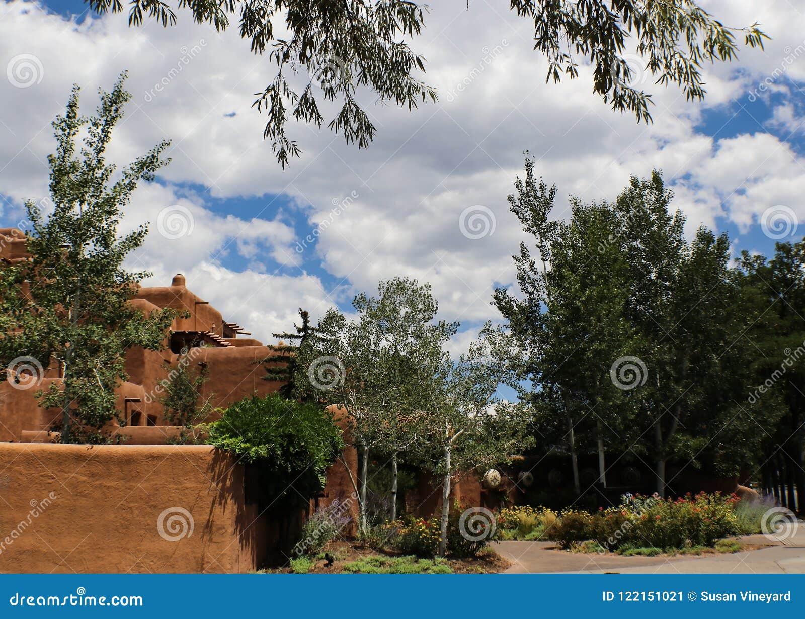 Arquitectura al sudoeste del adobe debajo de un cielo azul con las nubes blancas mullidas y rodeado y enmarcado por los árboles