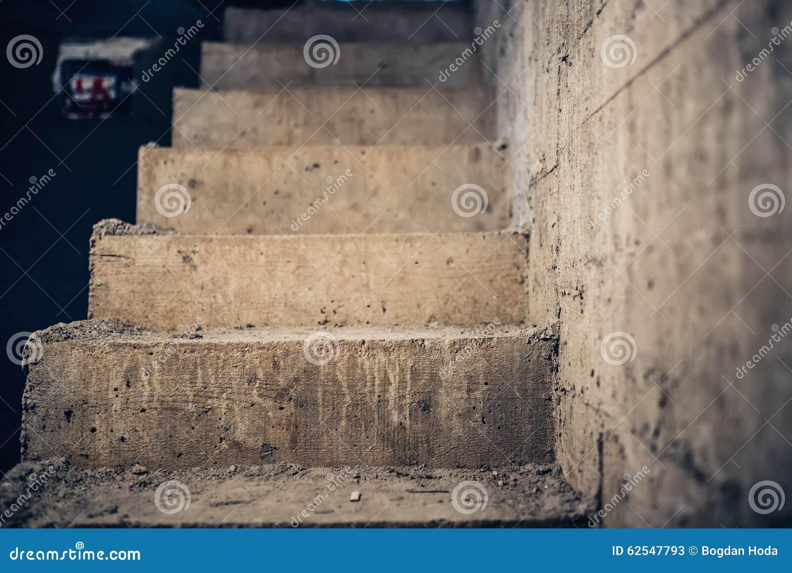 Arquitectura de las escaleras inacabada en el sótano Escalera concreta del cemento en el emplazamiento de la obra de la casa