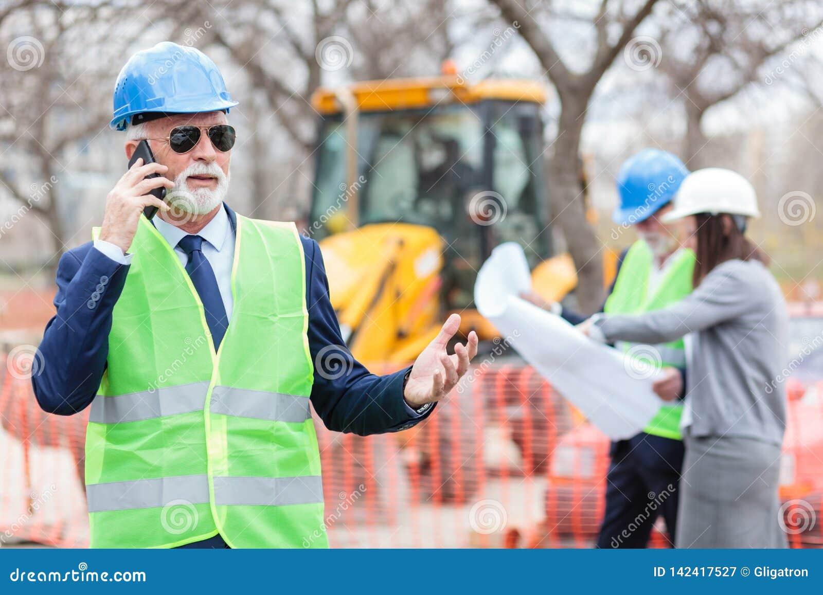 Arquiteto ou homem de negócios superior sério que falam no telefone ao trabalhar em um canteiro de obras