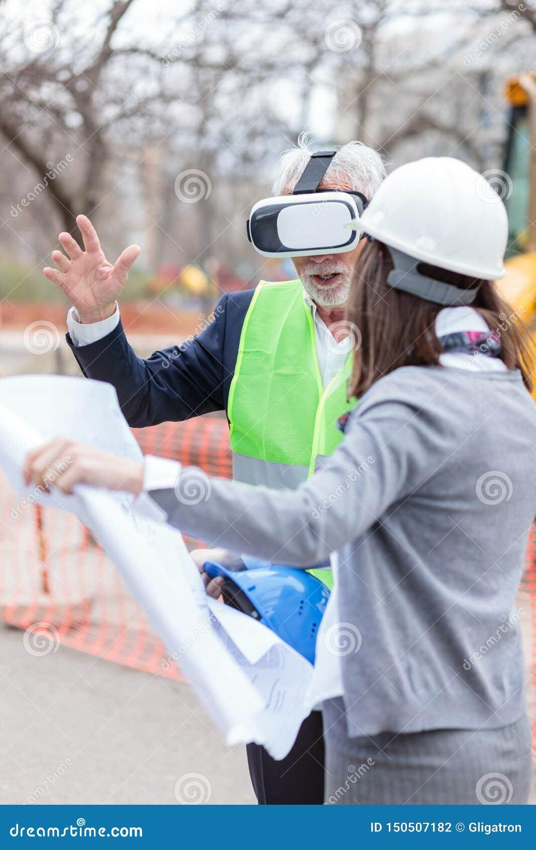 Arquiteto ou homem de negócios superior sério que usa óculos de proteção da realidade virtual para visualizar o projeto de constr