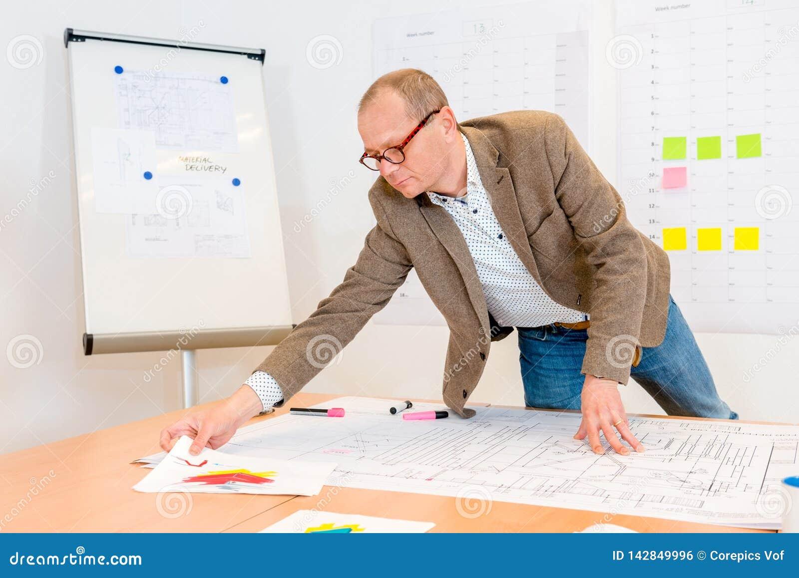 Arquiteto Reaching For Document ao trabalhar no modelo