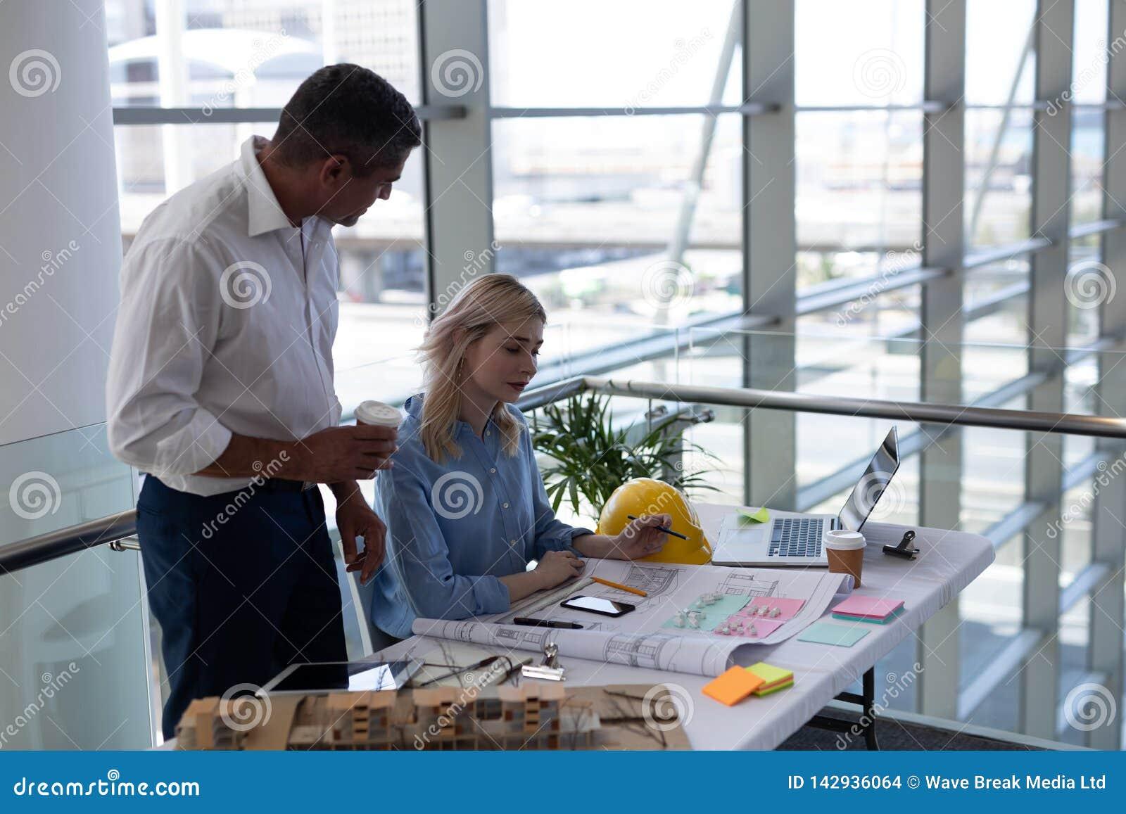 Arquitetos dos Caucasians que interagem um com o otro na mesa no escritório