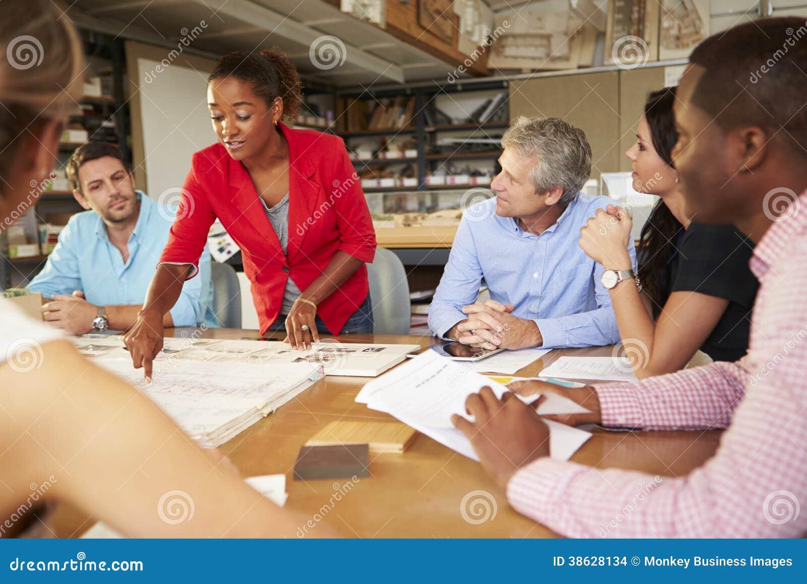 Arquitetos fêmeas de Leading Meeting Of do chefe que sentam-se na tabela