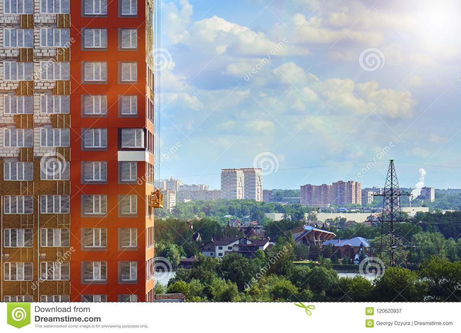 A arquitetura da cidade de Moscou com um trabalhador em um berço da construção na parede de uma construção sob a construção ilumi