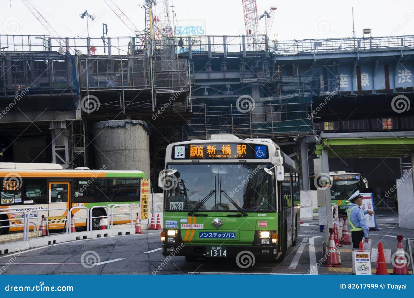 A arquitetura da cidade e o povo japonês conduzem o ônibus na estrada do tráfego e param-no