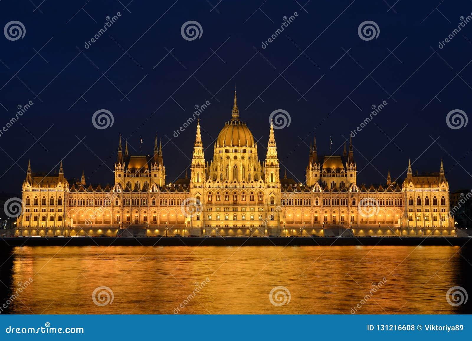 Arquitetura da cidade da noite da construção iluminada do parlamento de Budapest com reflexão dourada em Danube River