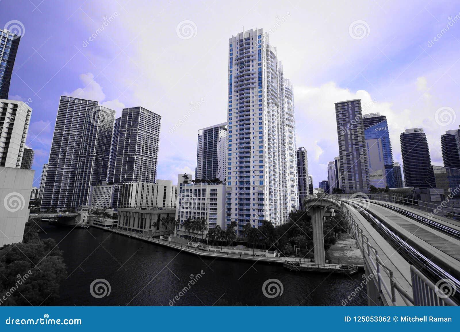 Arquitetura da cidade da skyline de Miami com construções altas e da ponte do trem sobre o rio em Brickell