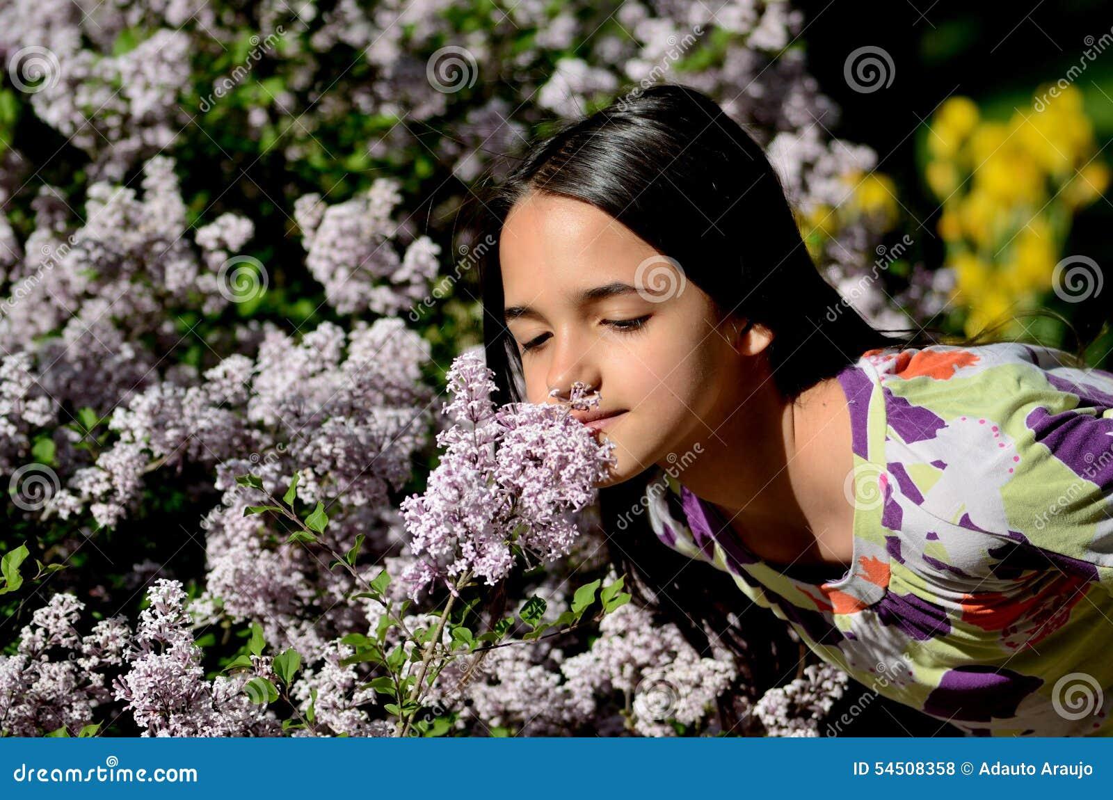 Arrêts de petite fille pour sentir les fleurs