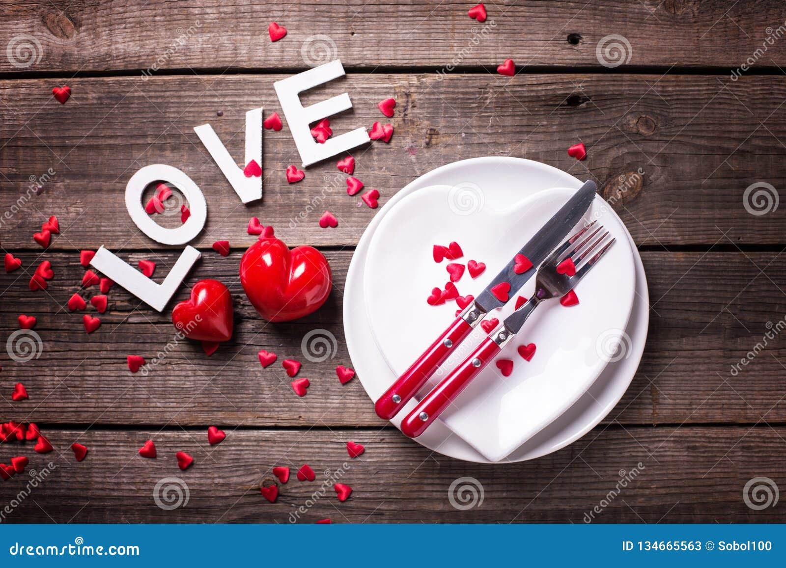 Arrangement de table de St Valentine Day Plats blancs sous la forme de coeur, de couverts, de coeurs décoratifs et d amour de mot