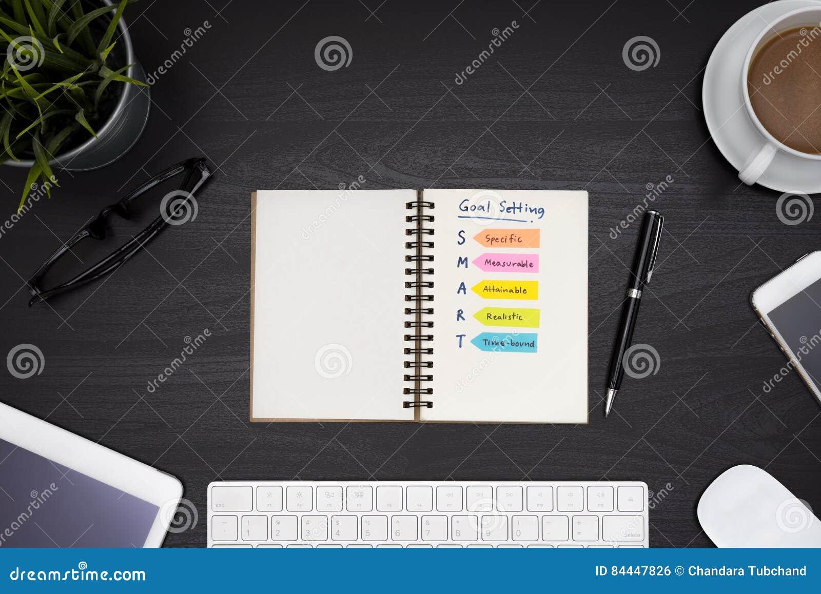 Arrangement futé de but sur le carnet au dessus du bureau noir de