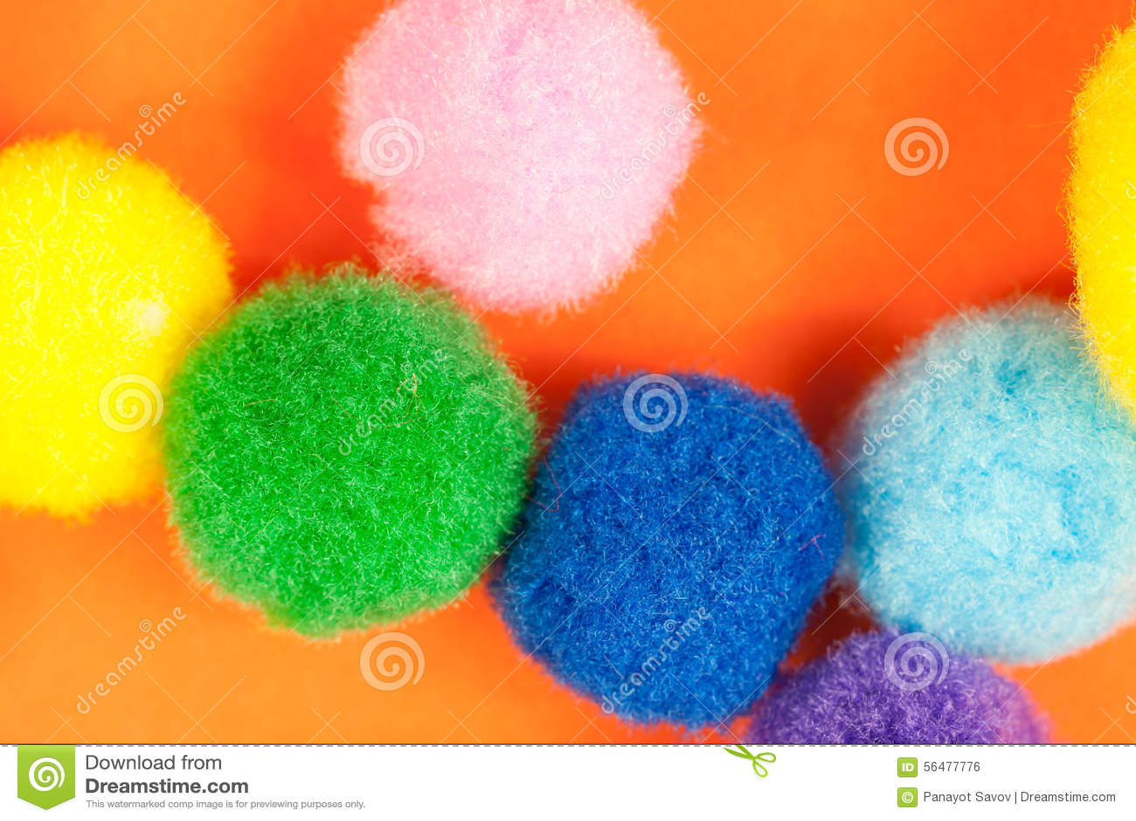 Arranjo de bolas macias de matéria têxtil distorcido macia colorida vívida no fundo de papel alaranjado vibrante