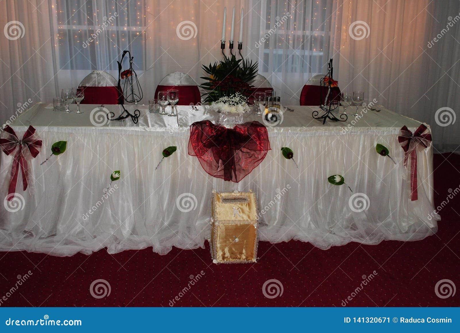 Arranjo do casamento com as cadeiras brancas e vermelhas que esperam convidados de g