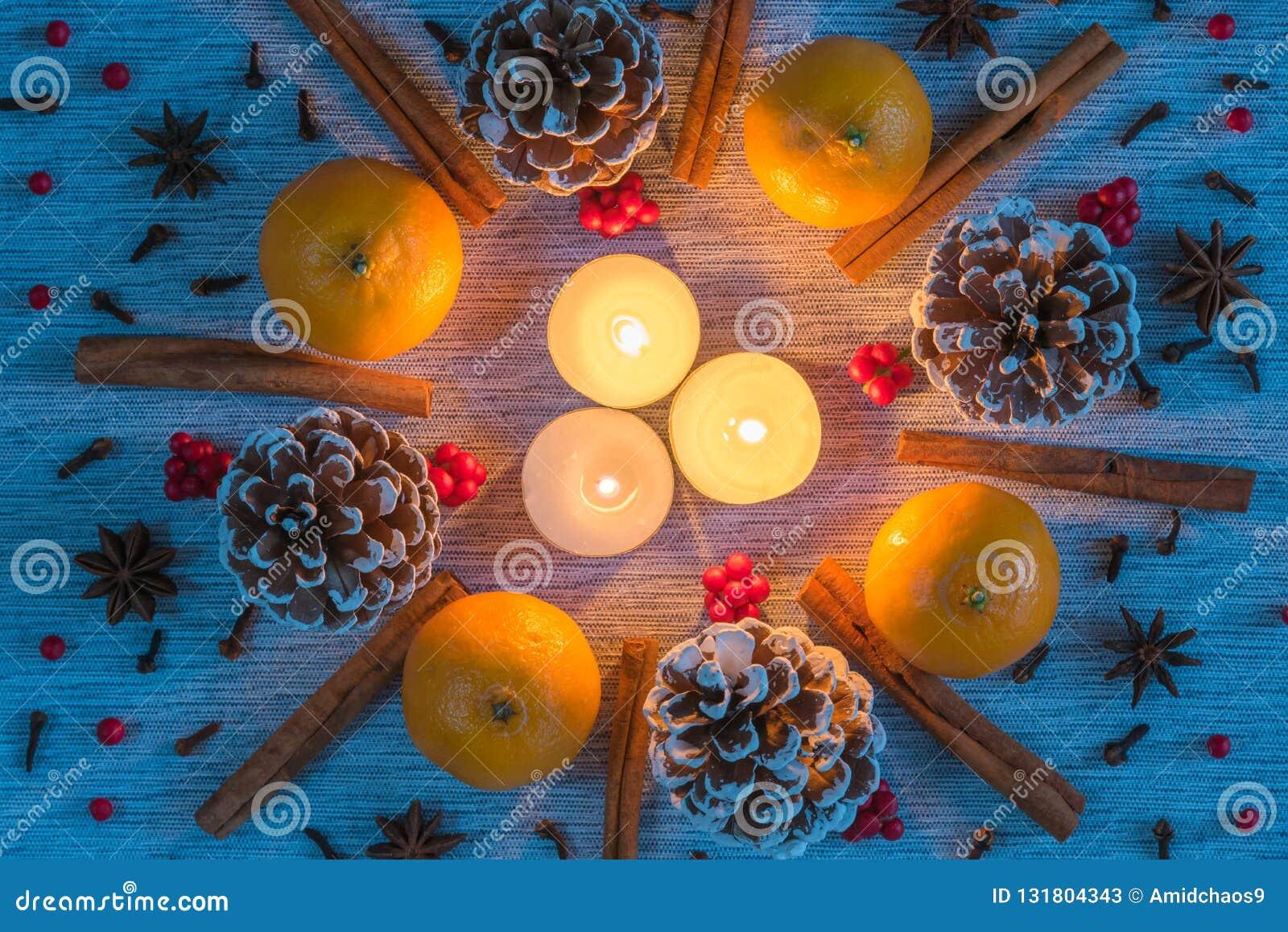 Arranjo do Natal das velas cercadas pela grinalda dos pinecones, laranjas, varas de canela