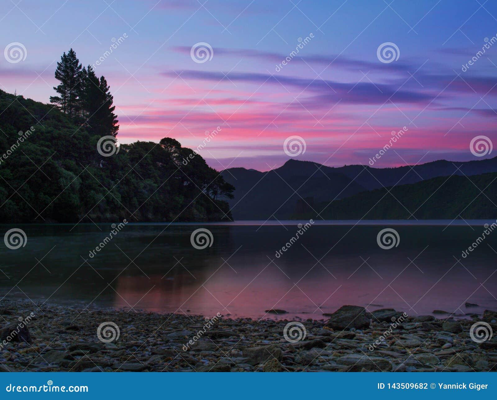 Arrebol da tarde bonito do por do sol que reflete no som de Kenepuru, Nova Zelândia