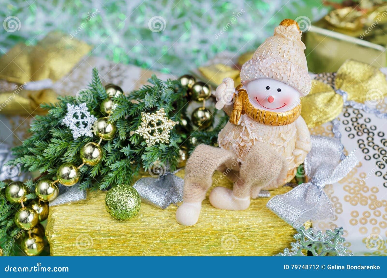 Arreglo de la Navidad en tonos del verde y del oro Muñeco de nieve alegre, decoraciones de los regalos
