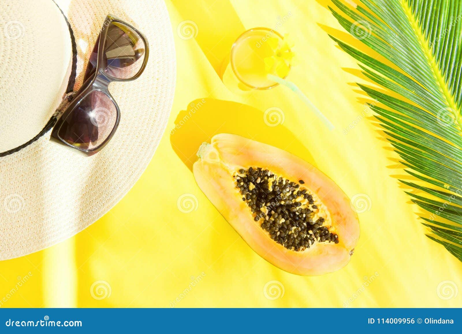 Arreglo plano de la endecha de Straw Hat Sunglasses Tall Glass con el fondo fresco de Juice Papaya Palm Leaf Yellow de la fruta t