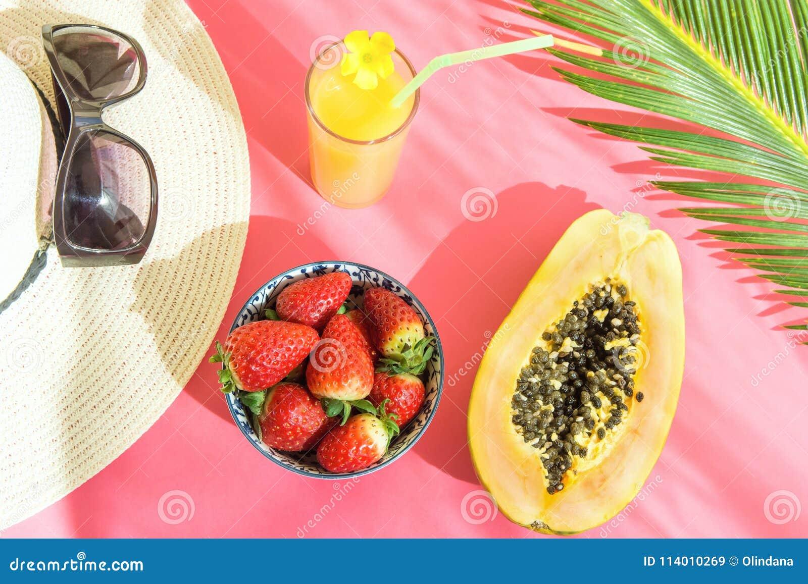 Arreglo plano de la endecha de Straw Hat Sunglasses Tall Glass con la fruta tropical Juice Papaya Palm Leaf de la fruta cítrica f
