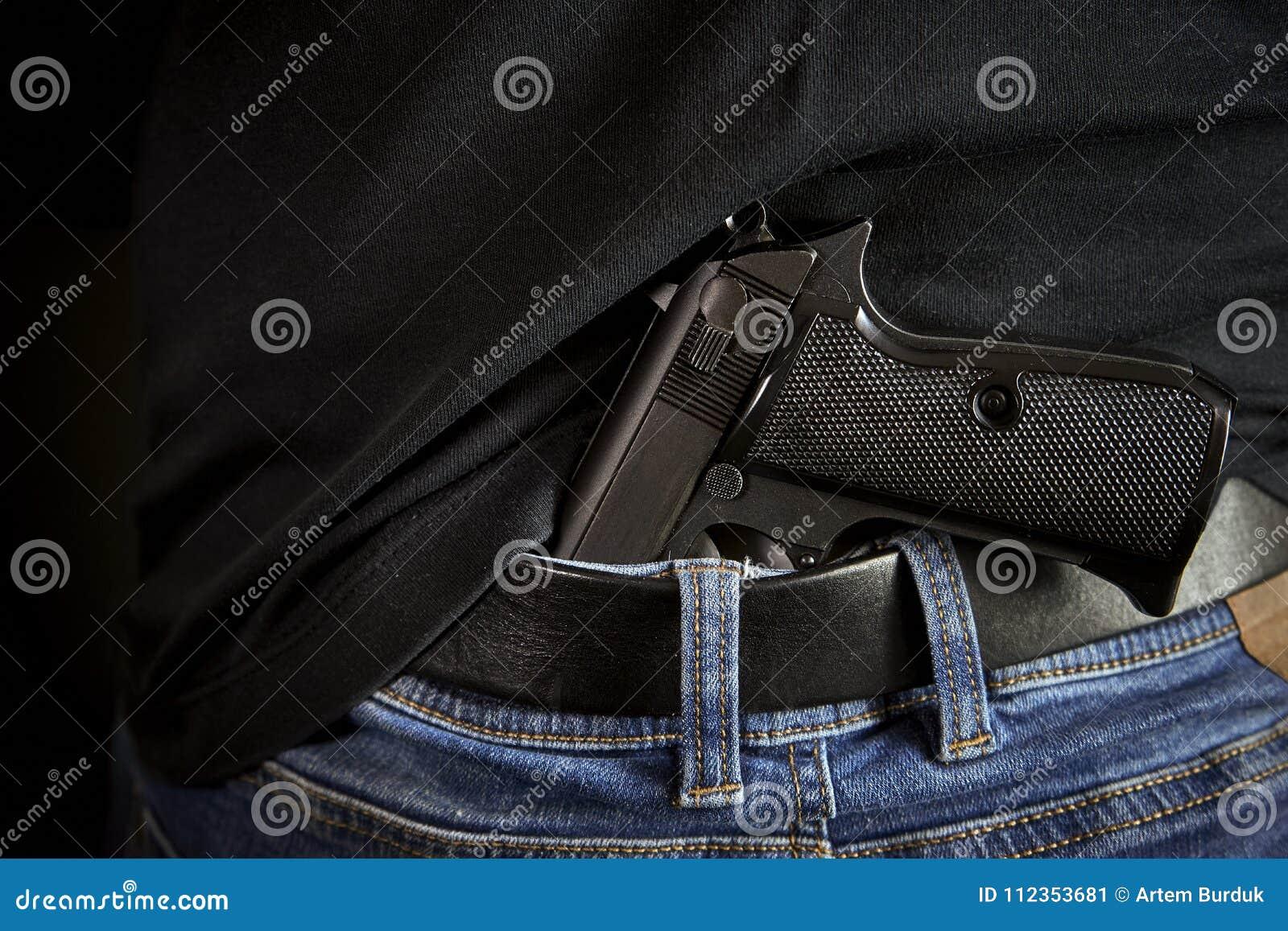 Arrière caché d arme à feu à l homme dans des blues-jean
