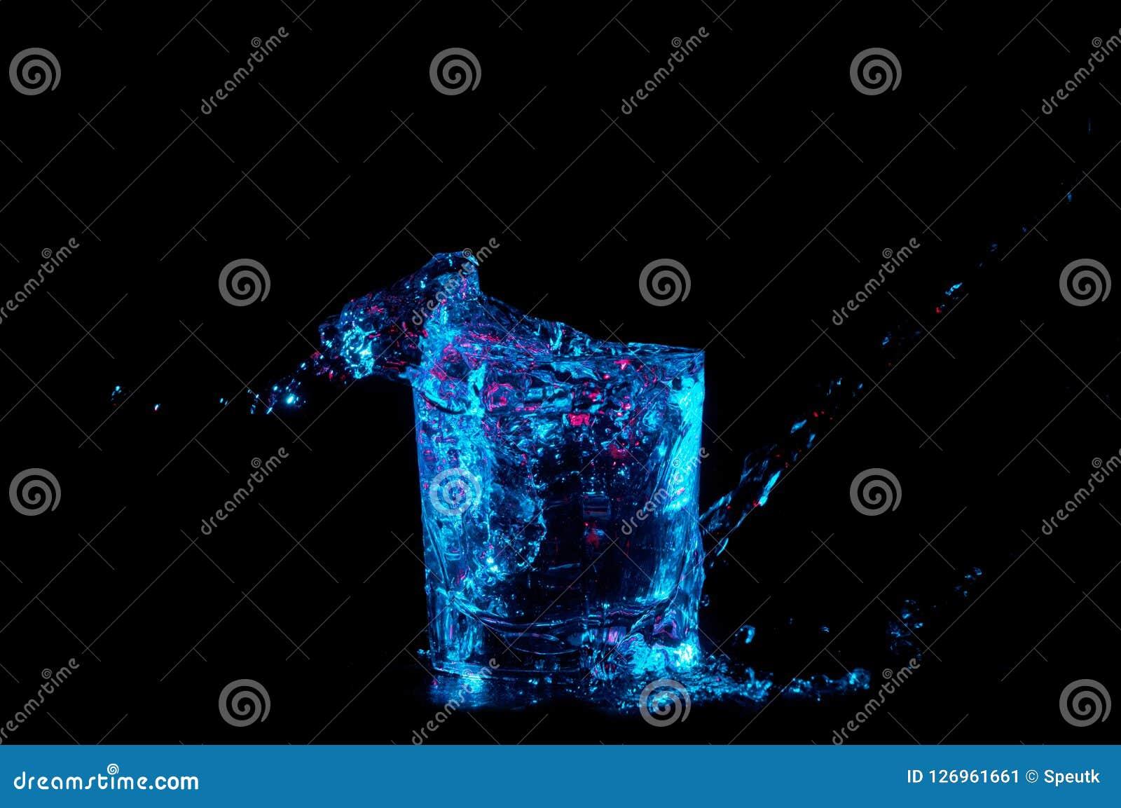 Arrosez éclabousser hors des lumières de roches bleu lumineux de dessous en verre et rouge d isolement sur un fond noir