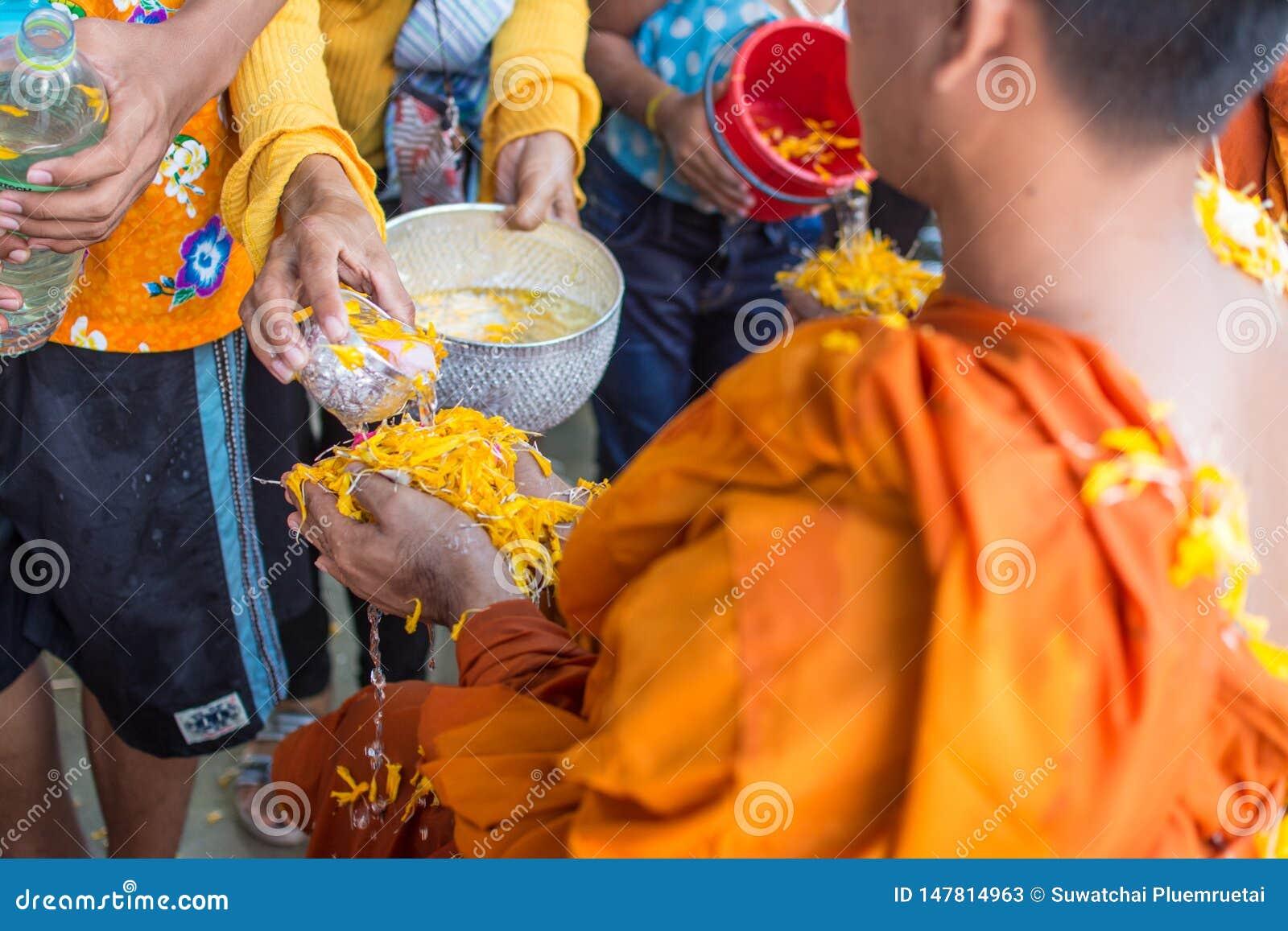 Arrosez le versement au moine dans la tradition de festival de Songkran de la Tha?lande