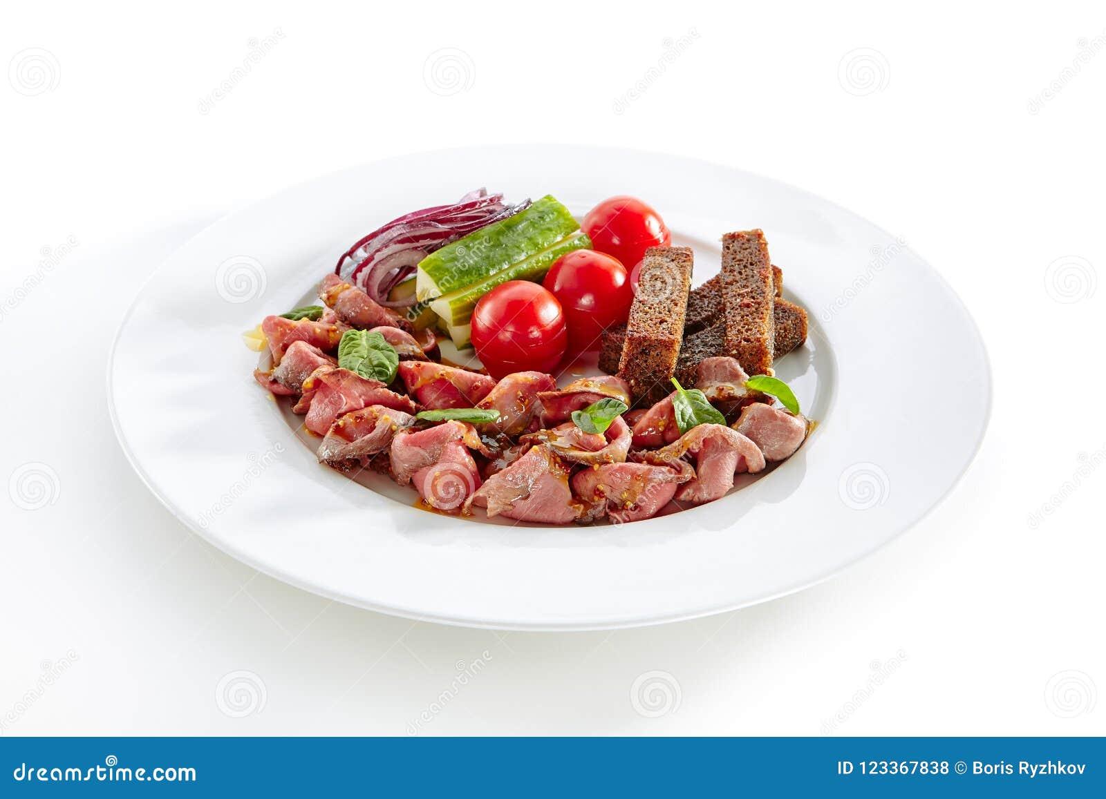 Arrosto di manzo piccante con gli ortaggi freschi isolati