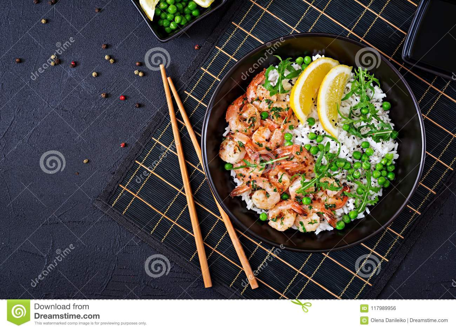 Arroz con los guisantes verdes, los camarones y el arugula jovenes en cuenco negro