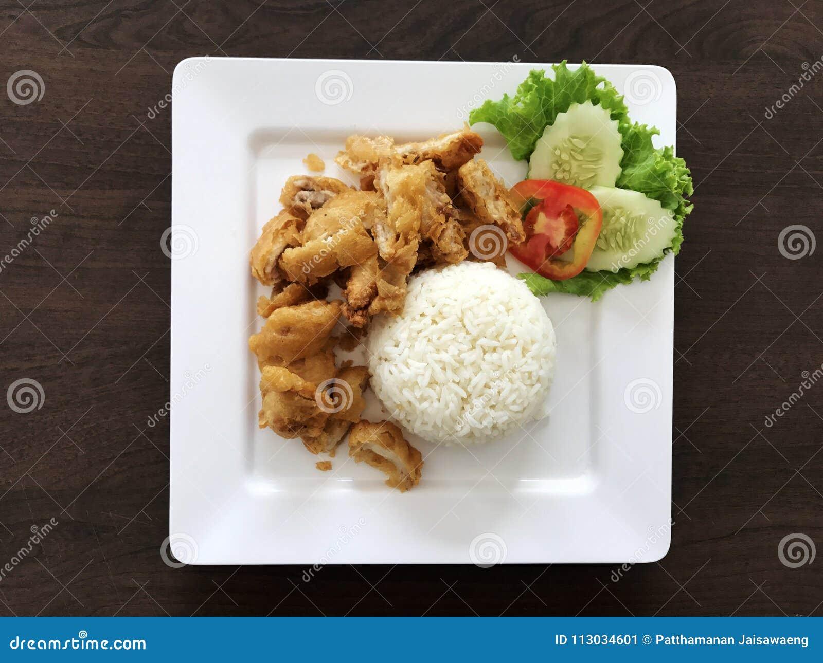 Arroz del pollo frito en el plato blanco en la tabla de madera