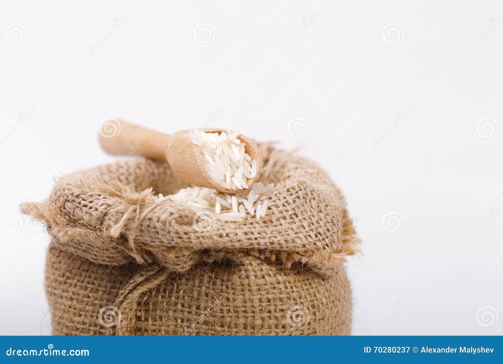 Arroz largo blanco en saco de la arpillera con la cuchara de madera imagen de archivo imagen - Saco arpillera ...