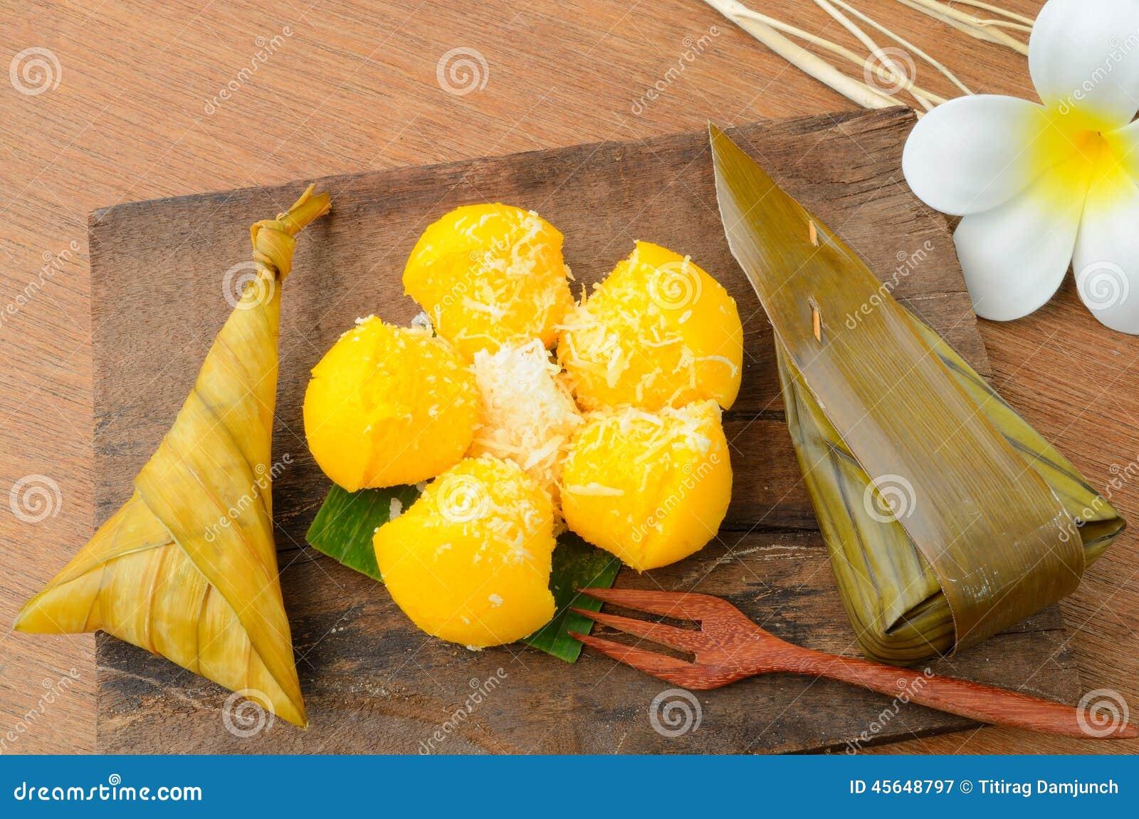 Arroz pegajoso da sobremesa tailandesa envolvido na folha da banana e o Toddy Palm Cake ou o Kanom Tarn
