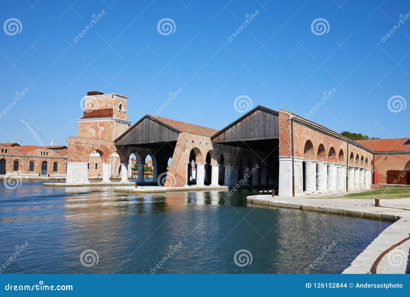 Arsenal veneciano con los muelles, canal y arcada, cielo azul en Venecia, Italia