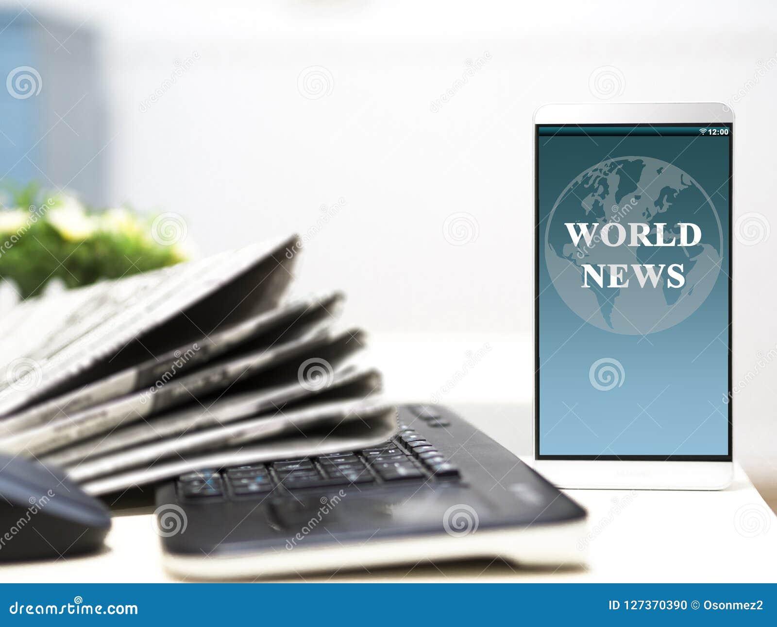 Artículo de noticias del mundo en su pantalla del smartphone periódicos con el teclado en la tabla