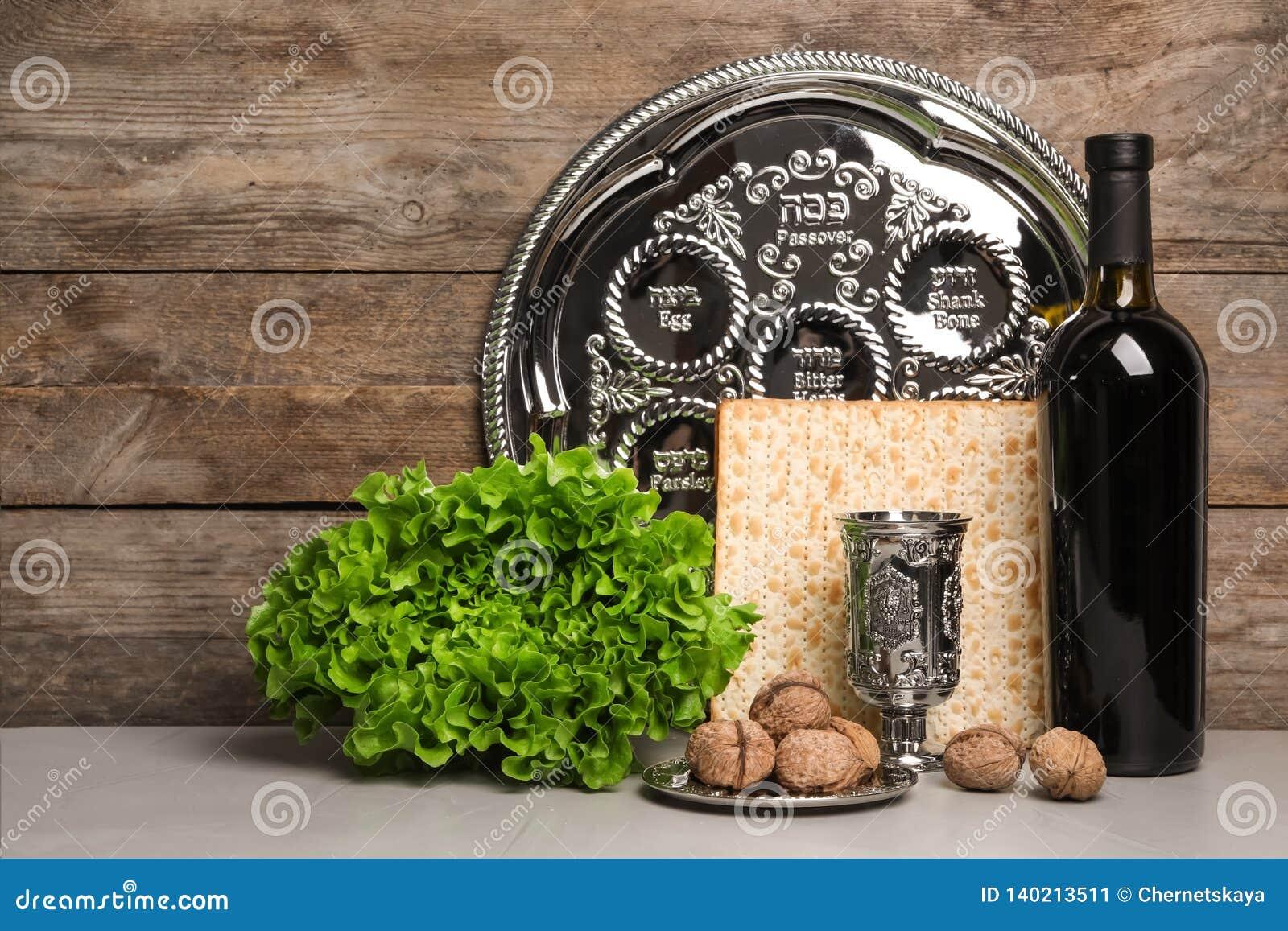 Artículos simbólicos de Pesach de la pascua judía en la tabla contra fondo de madera