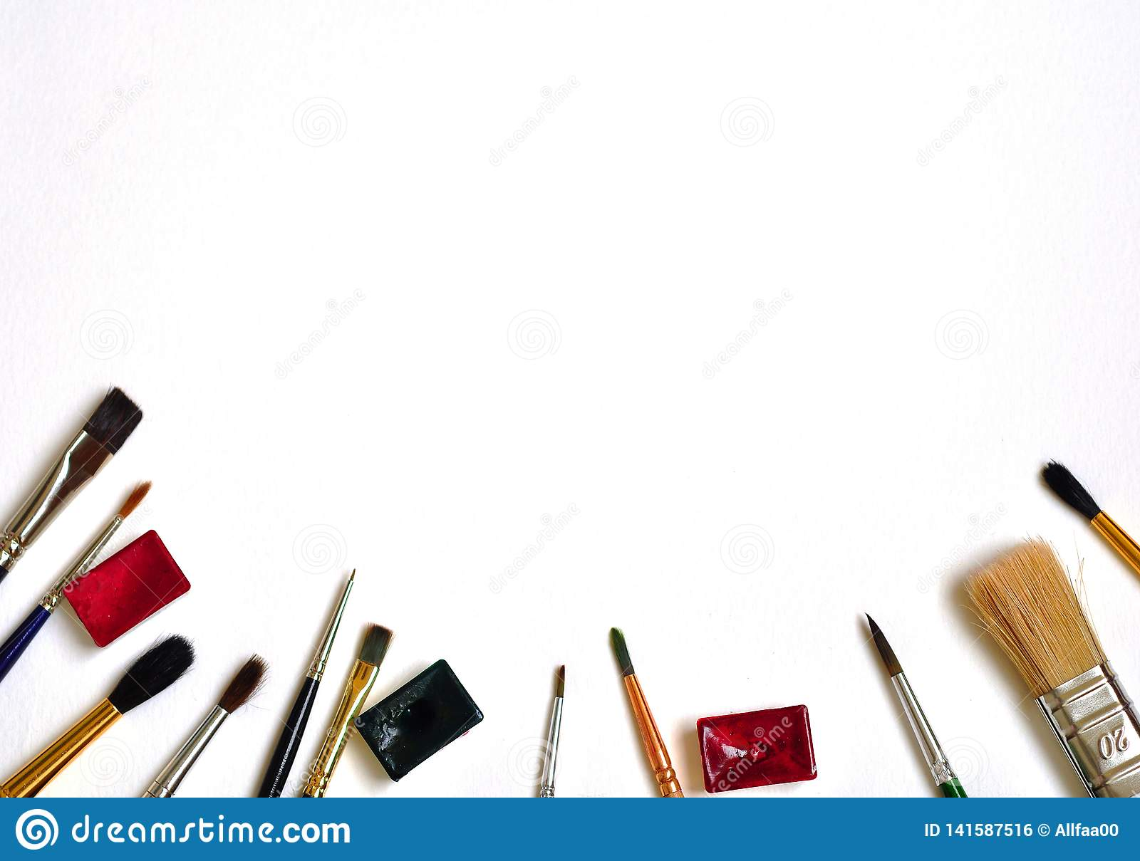 Art brushes and paints on a white background. Flat lay, top view, copy space