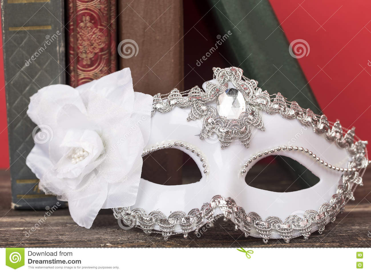 Art concept. Closeup of white classical carnival mask with vintage books and red background