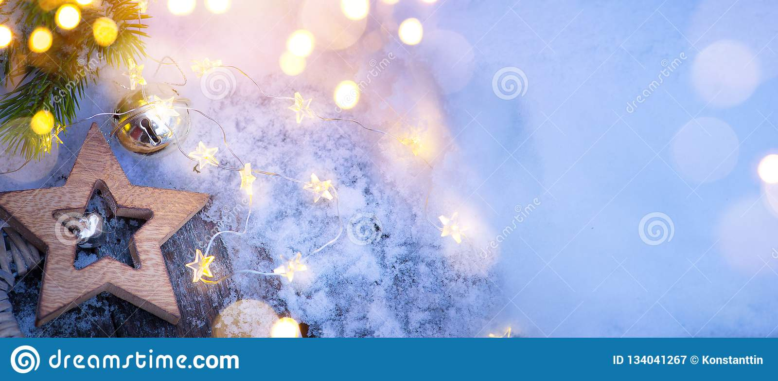 Merry Christmas blue snowy background and fir tree branches with holidays lights