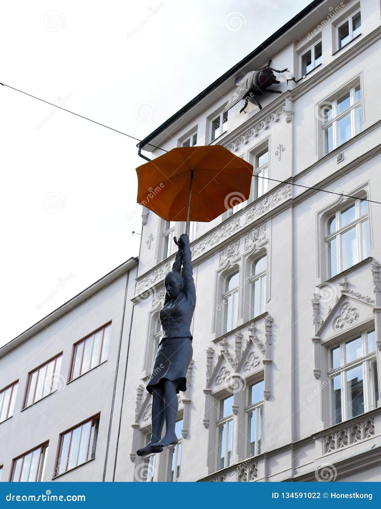 Art Performance avec la femme accrochant par le parapluie à Prague